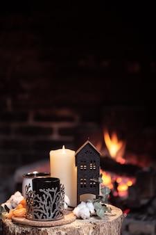 ホットドリンク、キャンドル、燃える火に対する装飾のある静物。暖炉のそばの夜のリラクゼーションのコンセプト。