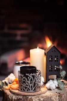 ホットドリンク、キャンドル、燃える火のある装飾のある静物。暖炉のそばで夜のリラクゼーションのコンセプト。