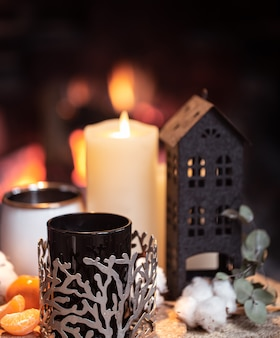 Still life with hot drinks, candle and decor against the background of a burning fire.