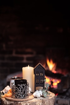 Natura morta con bevande calde, candele e decorazioni contro un fuoco ardente. il concetto di un relax serale vicino al camino.