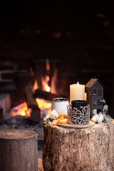 Still life with hot drinks, candle and decor with a burning fire. the concept of a village holiday outside the city.