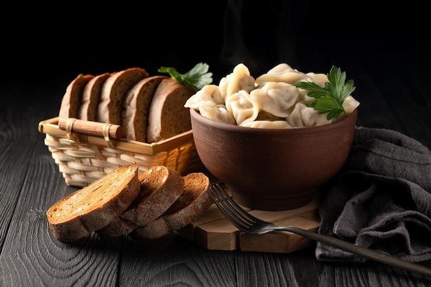 粘土のボウルに熱い餃子とトーストしたライ麦パンのある静物