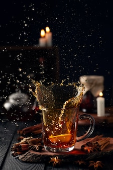Still life with hot tea with lemon spices and a beautiful splash from a glass