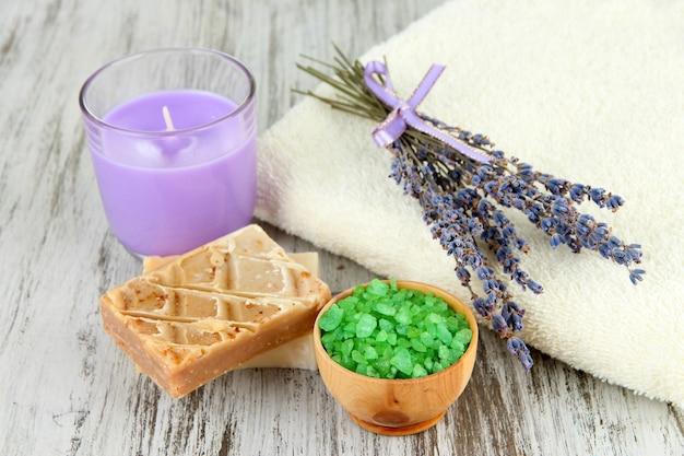 Натюрморт с лавандовой свечой, мылом, мылом и свежей лавандой, на деревянной поверхности