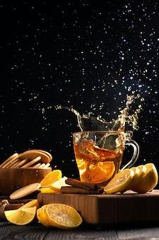 Натюрморт с лимонами и горячим чаем, чайные брызги разлетаются в разные стороны от упавшего лимона