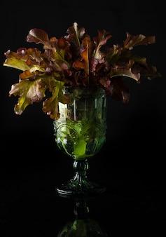 レタスの葉のある静物画は、反射のある低いキーに残ります。