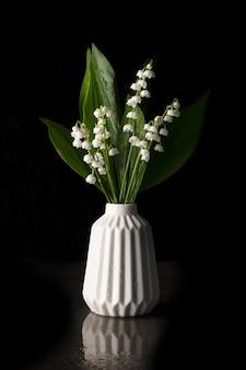 Натюрморт с ландышами в белой вазе на черном фоне. скопируйте пространство.