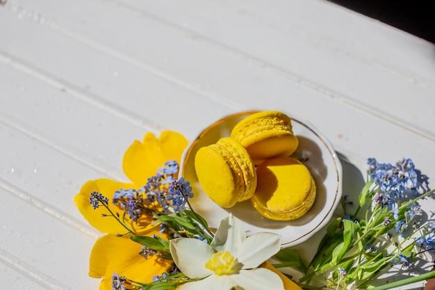 マカロンビスケットとflowers.lemonデザートのある静物。白い木製のテーブルにspace.frenchチョコレートデザートをコピーします。おいしいデザートフラットレイアウトと水仙とワスレナグサの花。