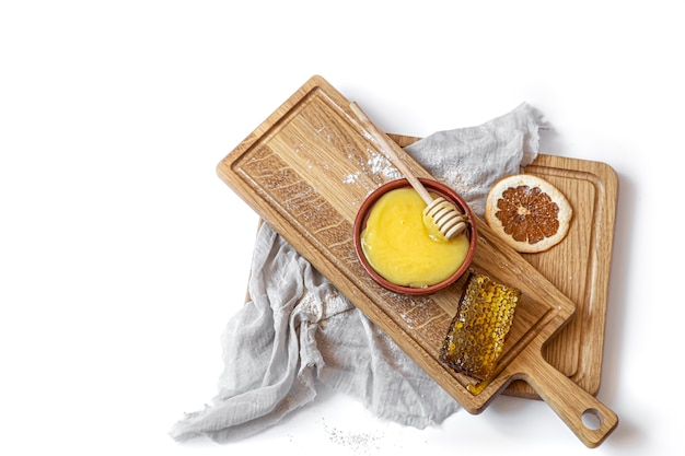 Still life with natural honey and honeycomb on a wooden plank close up isolated.