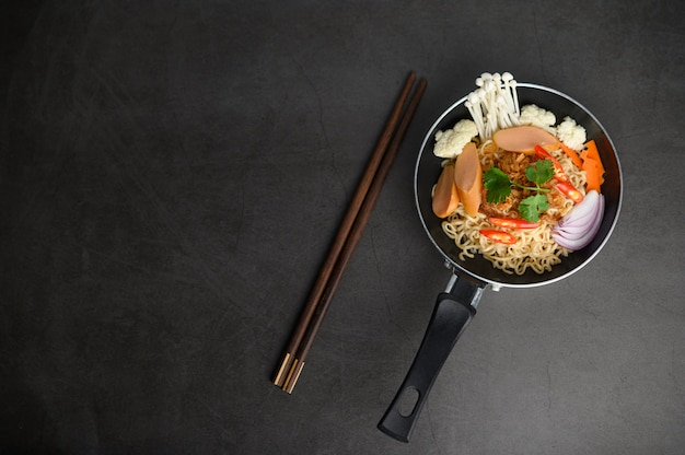 Still life with noodles in a pan and chopsticks.