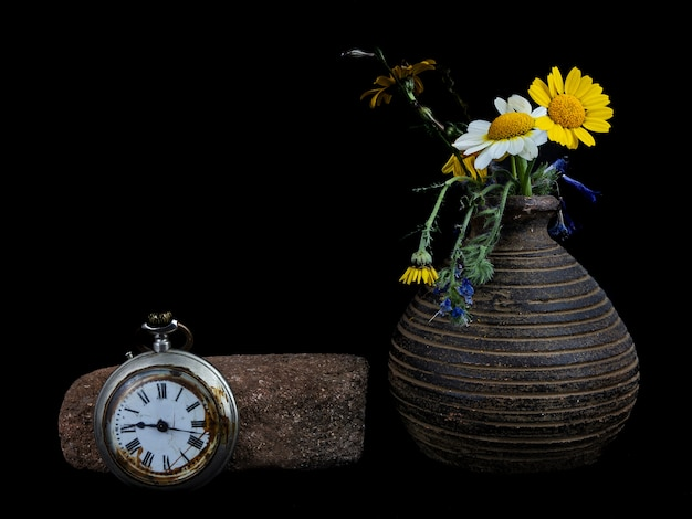 Still life with an old clock and wild flowers on black wall