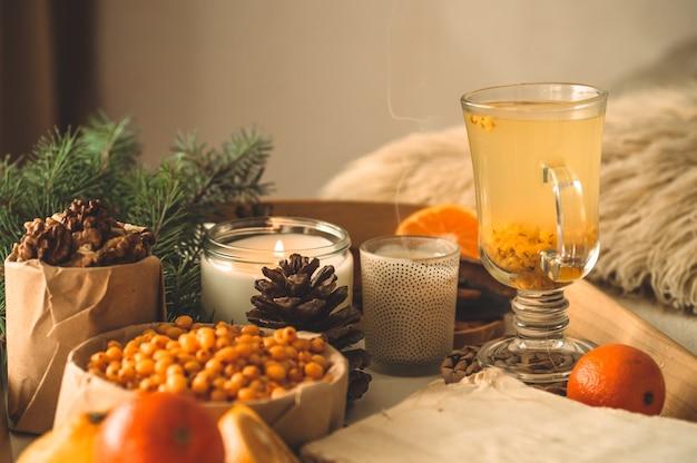 Натюрморт с апельсином и облепихой свеча, мандарины. концепция сезонных витаминов и здорового питания.