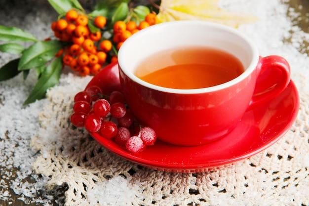 木製の背景に、カップ、ベリー、雪のオレンジ色のガマズミ属のお茶との静物