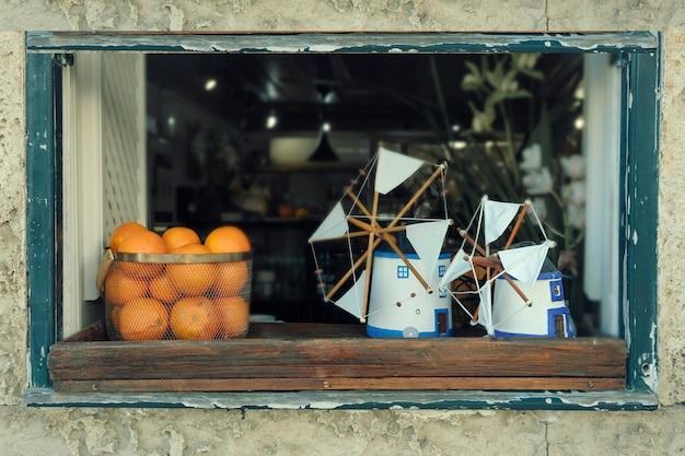 Натюрморт с апельсинами и игрушечными сувенирными ветряными мельницами на подоконнике в городе обидуш, португалия