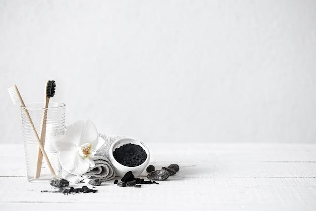 Natura morta con pennelli di bambù organico e polvere di carbone attivo e un fiore di orchidea come elemento decorativo. igiene orale e sfondo di cure odontoiatriche