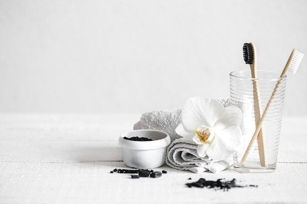 Still life with organic bamboo brushes and activated carbon powder and an orchid flower as a decorative element. oral hygiene and dental care.