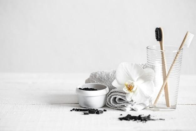유기농 대나무 브러시와 활성탄 가루와 난초 꽃을 장식 요소로 사용한 정물. 구강 위생 및 치과 치료.