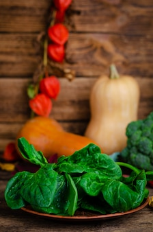 Still life with organic spinach on wooden rustic background