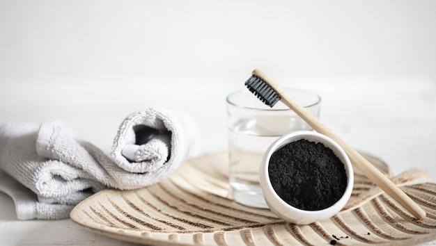 Natura morta con uno spazzolino da denti in legno biologico con un bicchiere d'acqua e polvere per sbiancamento dei denti naturale. igiene orale e cure odontoiatriche.