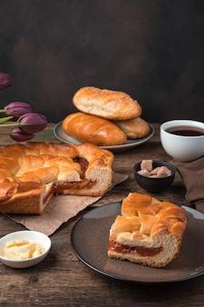 Натюрморт с выпечкой, пирогом с начинкой, булочками и чаем на коричневом фоне. вид сбоку, вертикальный