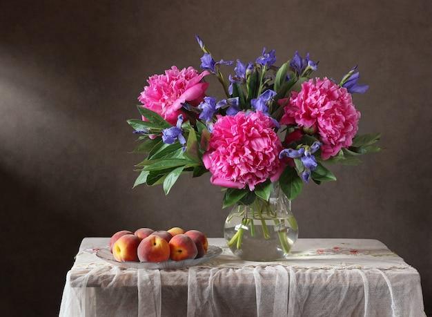 모란, 홍채 및 복숭아와 함께 아직도 인생. 용기와 과일에 정원 꽃입니다.