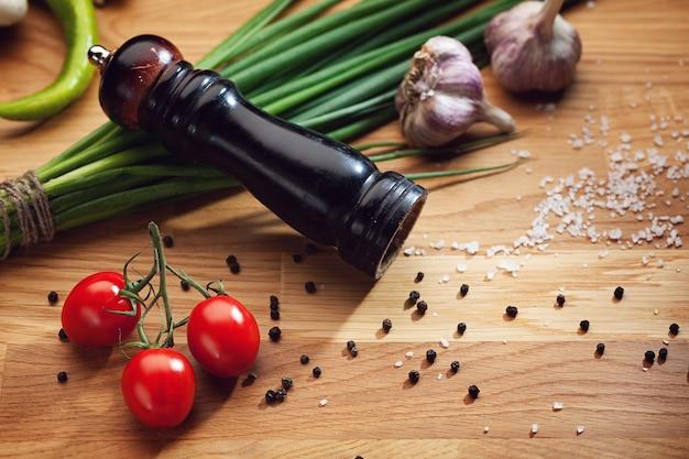 ペッパーミルとペッパーコーン、塩、トマト、ニンニク、ネギのある静物