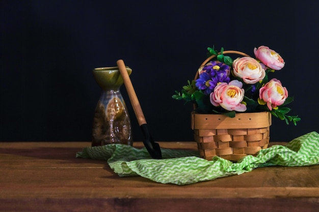 Still life with pink roses in basket on the table .