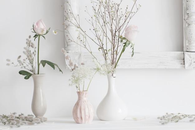 白い背景の上の花瓶に植物のある静物