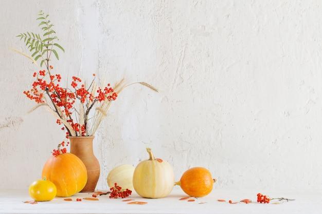 カボチャと木製のテーブルにナナカマドの枝のある静物
