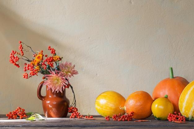 Натюрморт с тыквами и ветками рябины на деревянном столе