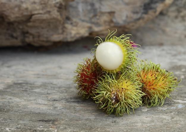 Натюрморт с тайскими фруктами рамбутан на деревянном пространстве