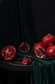 붉은 과일이 있는 정물, 식탁에 있는 녹색 벨벳 식탁보에 석류, 복고 스타일. 고품질 사진