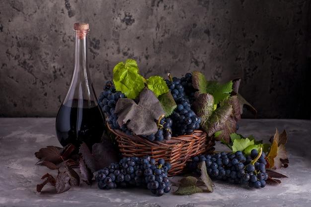 바구니에 붉은 포도와 와인 한 병 정