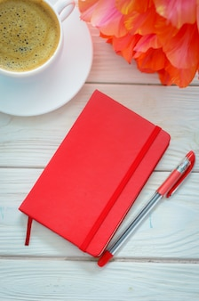 Still life with a red notebook and cup of coffee