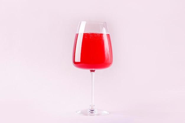 ワイングラスの分離されたピンクの背景にイチゴと赤のさわやかな夏のアルコールカクテルドリンクと静物