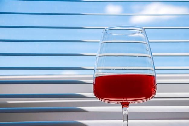 青い背景の上のワイングラスにイチゴと赤のさわやかな夏のアルコールカクテルドリンクと静物