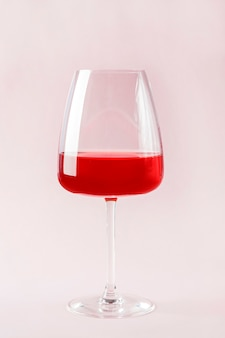 Still life with red refreshing summer alcoholic cocktail drink with strawberry in wine glass isolted on pink background