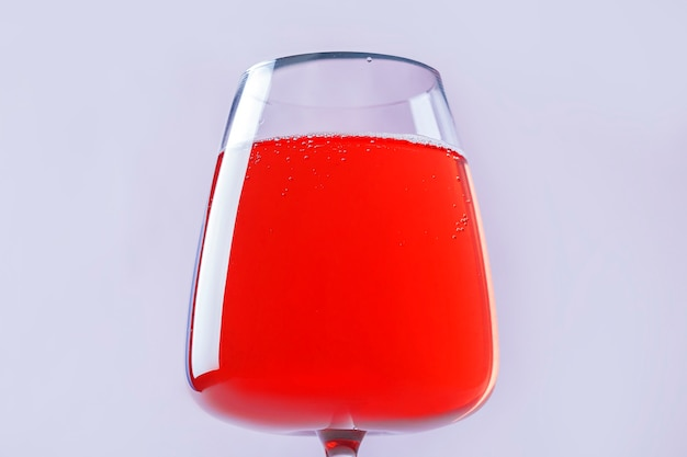 Still life with red refreshing summer alcoholic cocktail drink with strawberry in wine glass on pink background