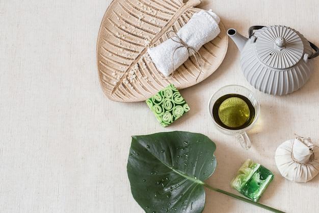 Natura morta con sapone, asciugamano, foglia e tè verde. concetto di salute e bellezza.