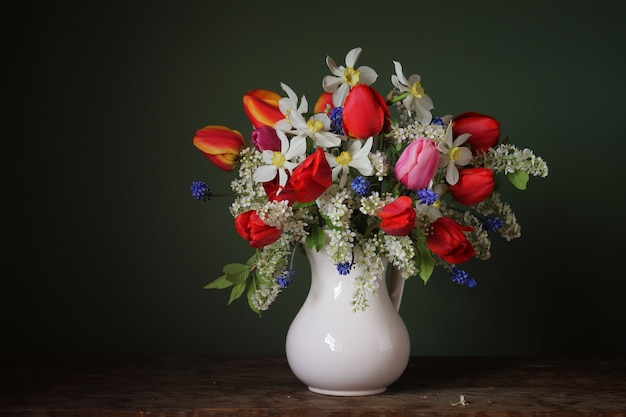 Still life with a spring bouquet in a white jug on a dark background.