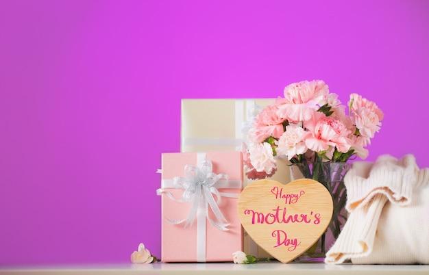 甘いカーネーションの花とテーブルの上の贈り物、母の日のコンセプトと静物