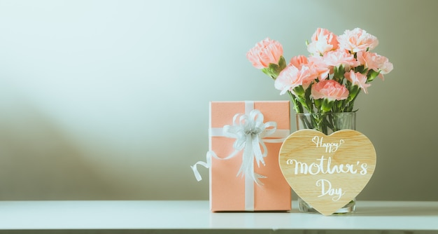 Still life with sweet carnation flowers and gift on table, mothers day concept, vintage filter color