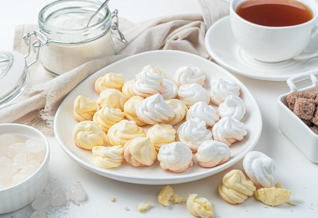 Натюрморт с швейцарскими безе, чаем, салфеткой и сахаром на светлом фоне. вид сбоку. вид сбоку.