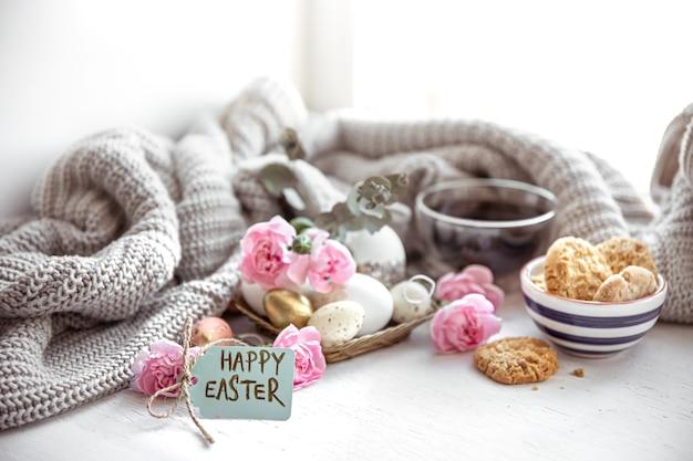お茶、クッキー、卵、花、はがきにハッピーイースターの碑文がある静物。