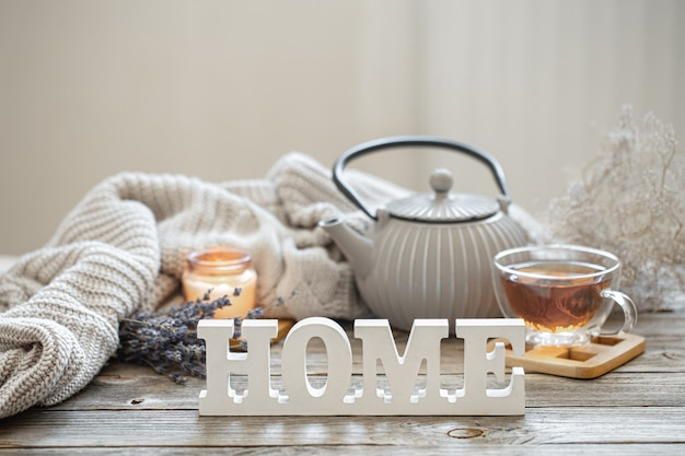Натюрморт с чайником и чаем на деревянной поверхности с вязанным элементом, уютными деталями и декоративным словом дома