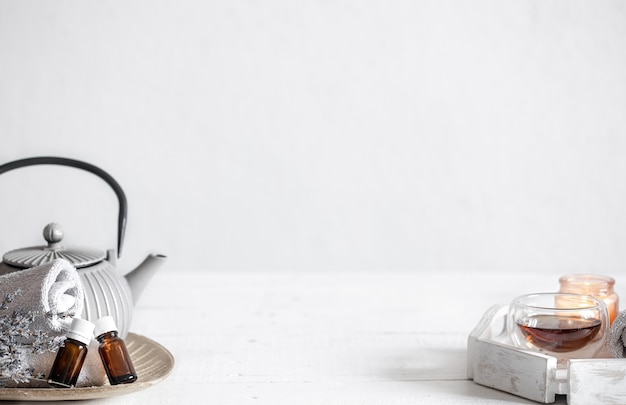 Still life with a teapot, tea, oil bottles and lavender sprigs. aromatherapy and health care concept background