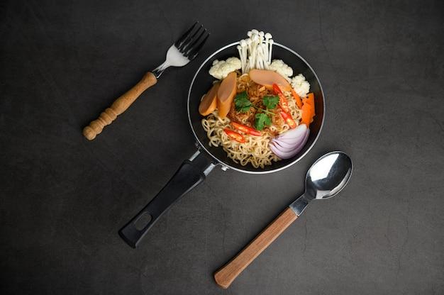 Натюрморт с лапшой в сковороде, вилке и ложке на черном цементном полу.