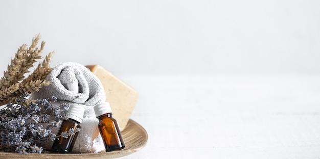瓶に入ったタオル、石鹸、アロマオイルのある静物。