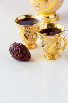 Still life with traditional golden arabic coffee set with dallah and cup of tea. ramadan concept.