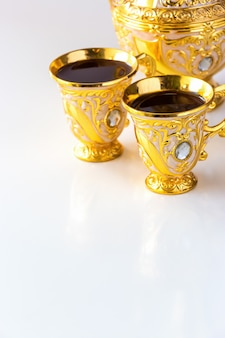 Still life with traditional golden arabic coffee set with dallah and cup of tea.